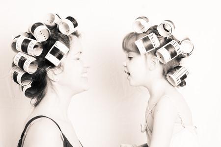 moeder en dochter met rollen in hun haar hebben fonds samen