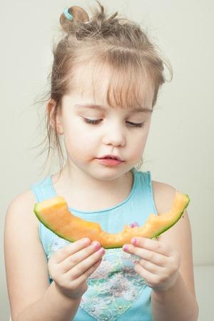 preschool age little girl eating a slice of cantaloupe