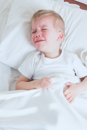 sick toddler boy wearing white tshirt crying in bed
