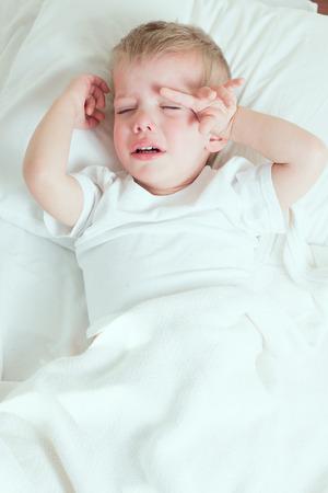 zieke peuter jongen draagt een witte t-shirt huilen in bed Stockfoto