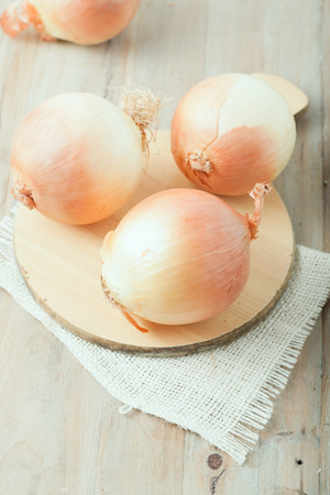 three onions on chopping board on wooden rustic background Banco de Imagens