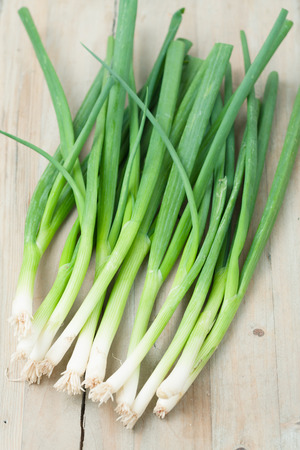 a bunch of green onions isolated on wooden background photo