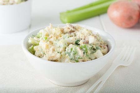 mayonesa: Ensalada de patatas casera ingredientes incluyen palitos de apio y hierbas en un recipiente blanco Foto de archivo