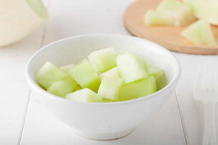HONEYDEW: chopped honeydew melon in a white bowl Stock Photo