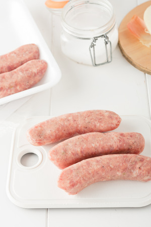 mild: store bought uncooked meat sausages on white chopping board, on white background