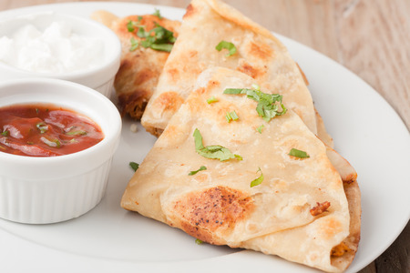 original mexican quesadilla garnished with cilantro on white plate with sour cream and salsa