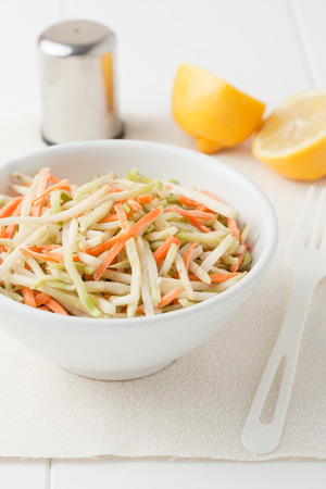 shreded: a white bowl of broccoli slaw shreded broccoli stalk and carrots  with lemons in the background