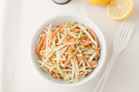 shreded: a white bowl of broccoli slaw shreded broccoli stalk and carrots  with lemons in the background, top view Stock Photo