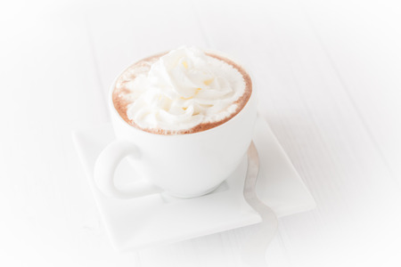 vignetted: a cup of coffee with wheap cream with white background, vignetted