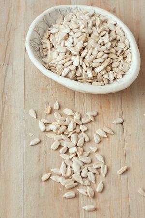 hulled: hulled sunflower seeds in small bowl on wooden rustic background