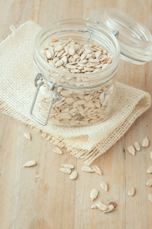 hulled: hulled sunflower seeds in  glass jar on wooden rustic background