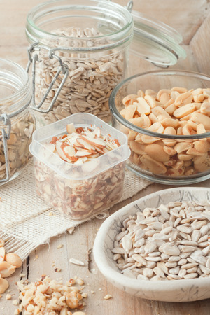 various nuts and seeds in various containers on wooden background photo