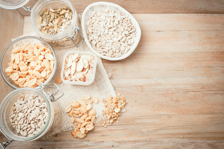 various nuts and seeds in various containers on wooden background, top view with room for text photo