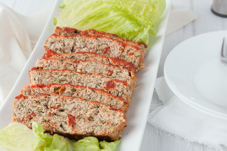 meatloaf: a serving platter of sliced turkey meatloaf with spinach and sundried tomatoes