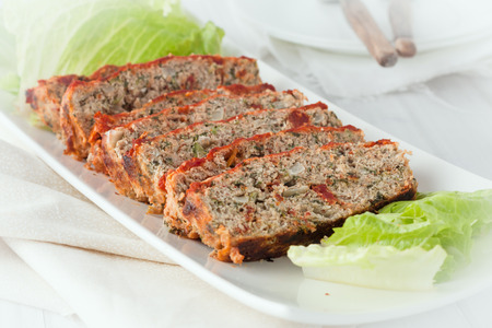 un plato de servir de rebanadas de pastel de carne de pavo con tomates secados al sol y espinacas Foto de archivo