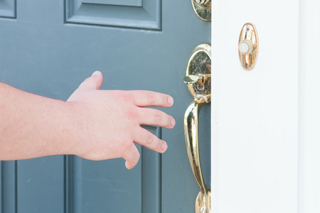 close up of mans hand about to open front door photo