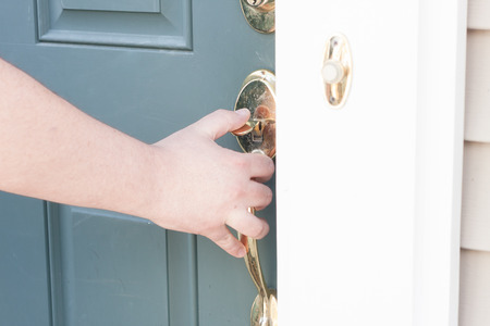red handed: close up of mans hand opening front door