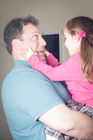 little girl being playing and making faces with her dad