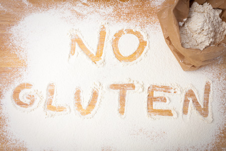 no: the words NO GLUTEN written on gluten free flour, overhead view