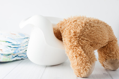 misbehaving: Teddy bears head stuck in the potty - conceptual image representing potty training in young age troubles.