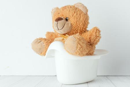 Een teddybeer in een wit potje naast stapel van luiers. Conceptueel beeld vertegenwoordigt zindelijkheidstraining