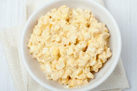homemade egg salad in white bowl on white background