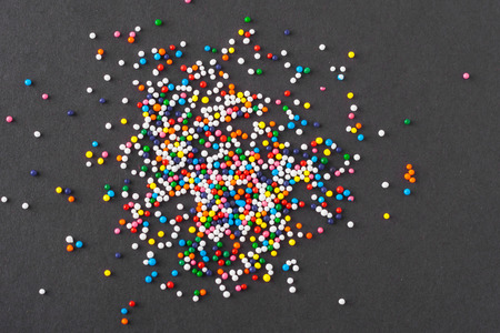 black textured background: Colorful sprinkles spilled on black textured background Stock Photo