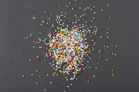 Colorful sprinkles spilled on black textured background photo