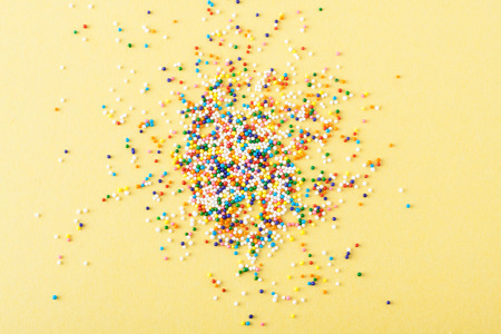 Colorful sprinkles spilled on yellow textured background photo