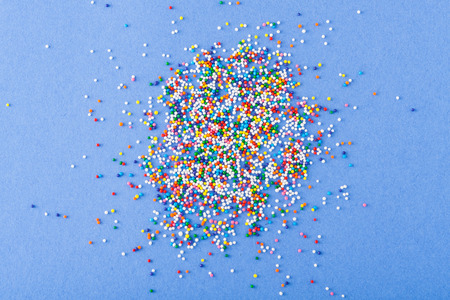 Colorful sprinkles spilled on blue textured background photo