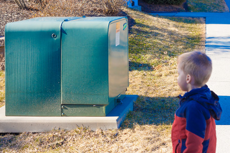 a toddler boy looking at a high voltage transformer outside his home