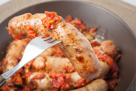 close up of oven cooked sausage on a fork baked with garlic, tomatos and italian herbs