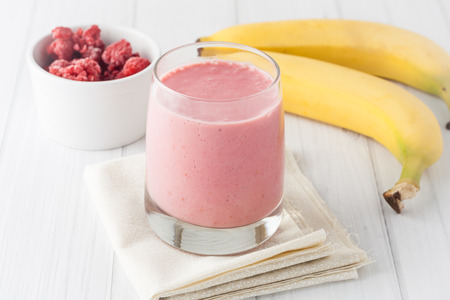 banana: a glass of fresh homemade frozen raspberries and banana smoothie on white background Stock Photo