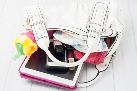 contents of a mother's white shoulder bag on white background