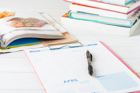 Monatskalender und Stapel von Kochbüchern. Konzeptionelle Bild zeigt Mahlzeit Planung im Gange. Geringe Schärfentiefe, Standard-Bild