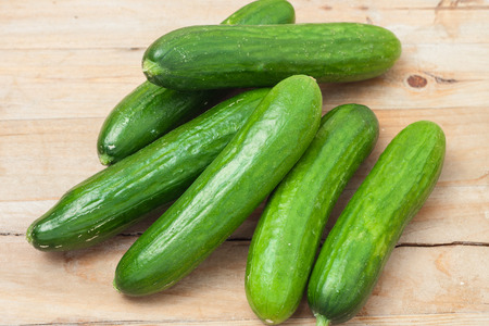 a pile of fresh picked cucumbers on wooden background