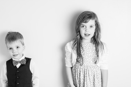 in unison: black and white portrait of brother and sister getting talked to by a parent, standing against a wall, great parenting image