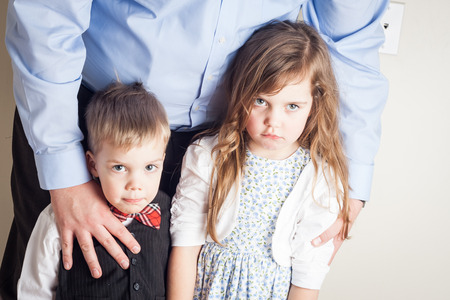 brother and sister held by their father, with guilt on their faces, great parenting image