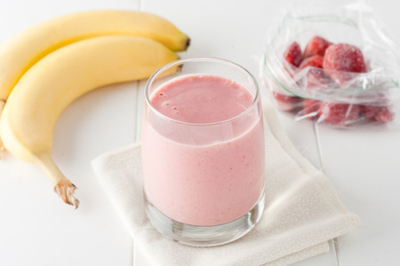 banana: a glass of homemade banana and frozen strawberry smoothie on white background