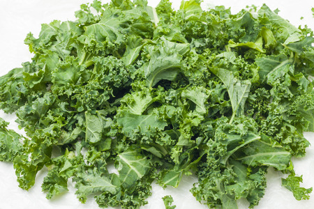 loose chopped kale leaves on white background