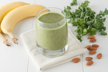green smoothie on white background, ingredients include bananas, fresh kale and almonds