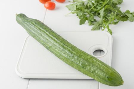 english cucumber: whole organic English cucumber on white chopping board Stock Photo