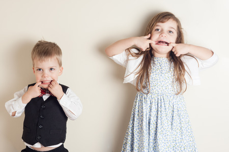 misbehaving: brother and sister standing against a wall and making faces
