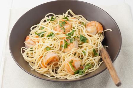 close up of a brown bowl of shrimp scampi
