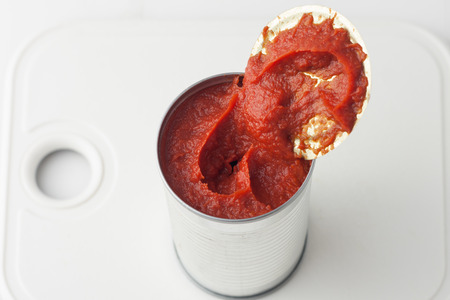 tomato paste: opened can of tomato paste on white cutting board