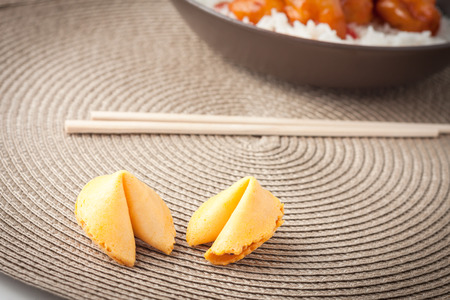two chinese fortune cookies on brown place mat photo
