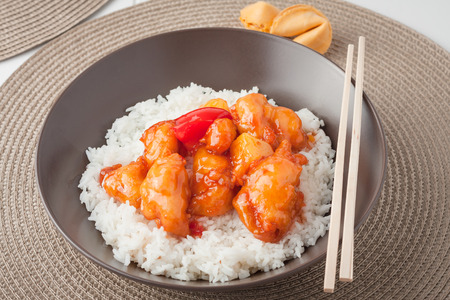Sweet and sour chicken with rice in brown bowl photo