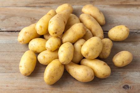 papas: patatas bebé primas en el fondo de madera rústica