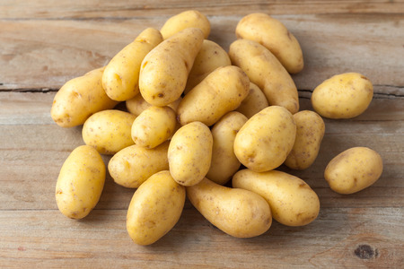 baked potatoes: raw baby potatos on rustic wooden background