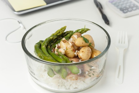 a glass container with lunch with leftovers on a desk at work photo